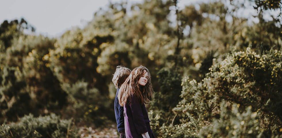 Two adolescents on a walk in the woods.