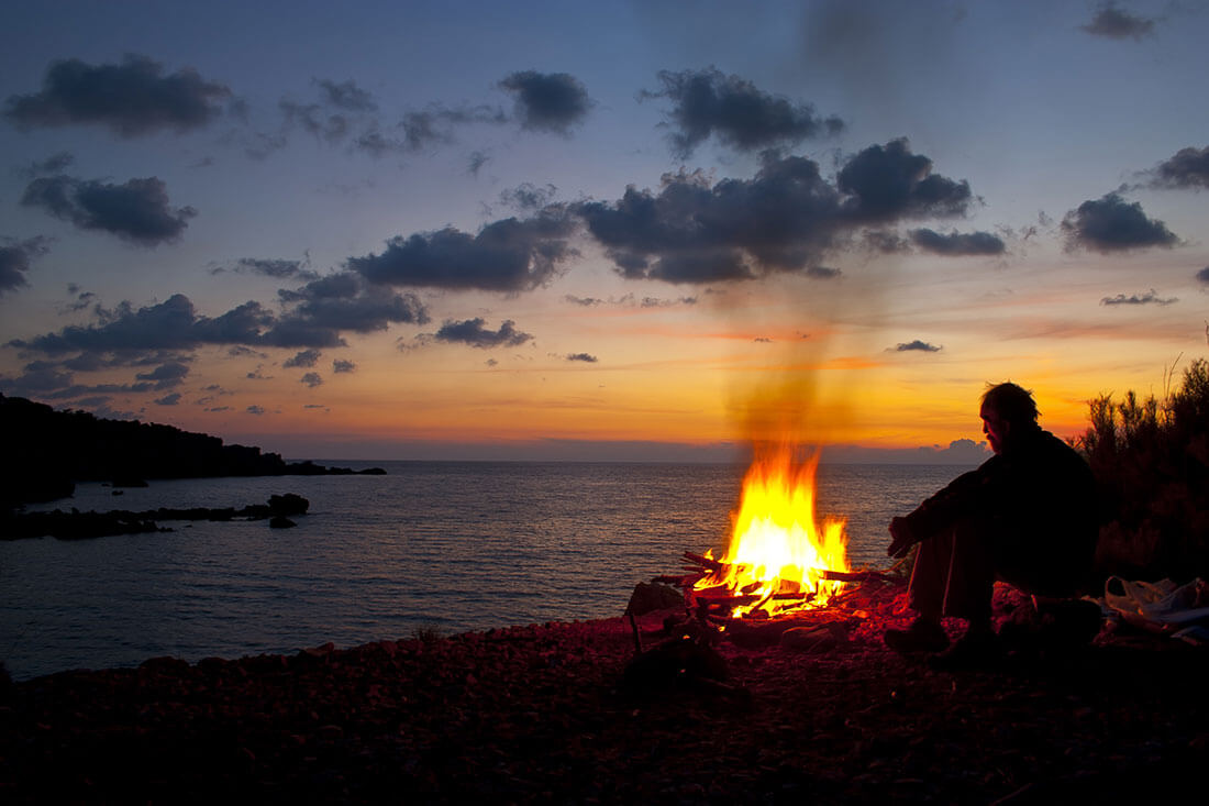 Man sits next to campfire while the sun sets on a bay.