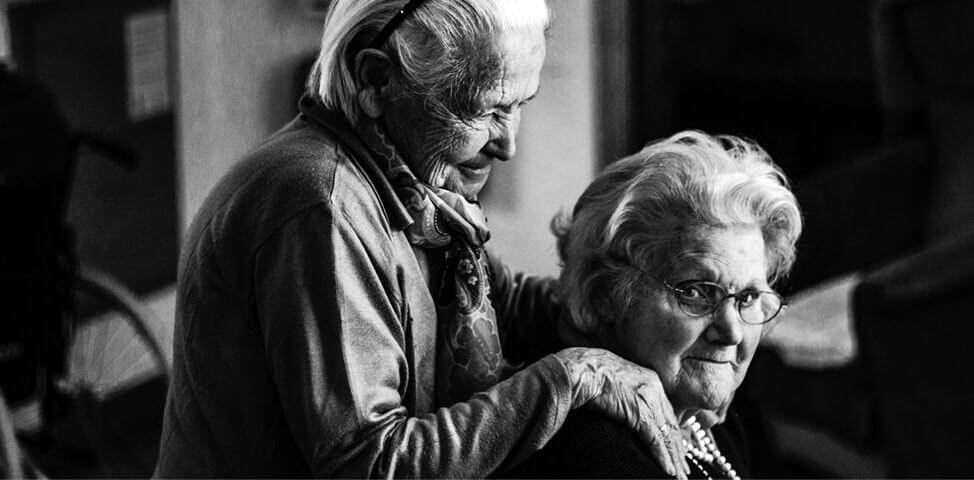 Two elderly women supporting each other.