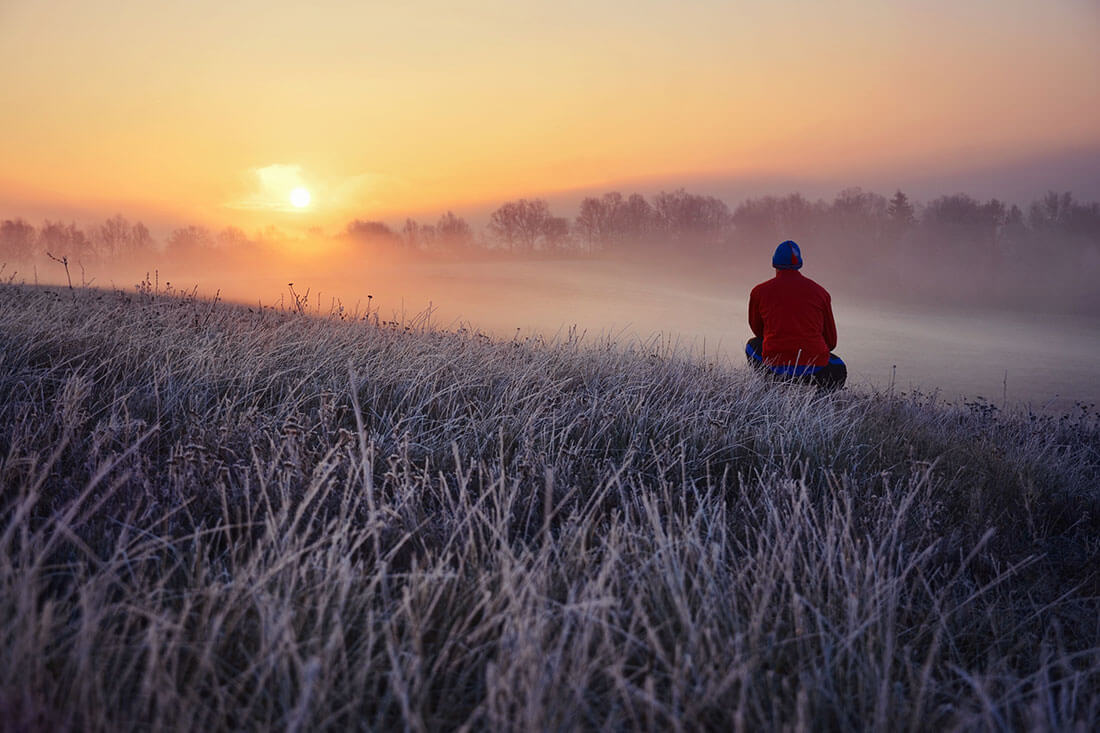 Young man standing in winter frozen nature and watching to the calm winter misty sunrise