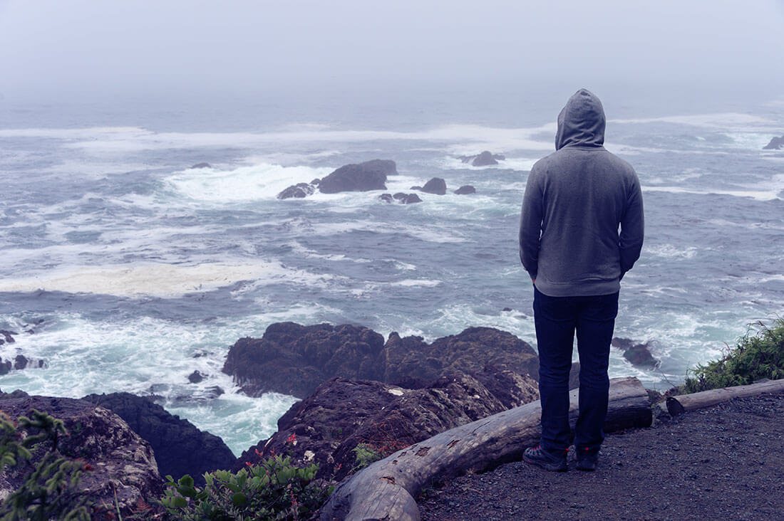 Grieving man looks out at the stormy ocean.