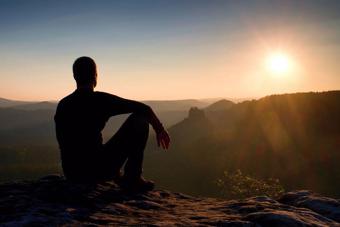 Grieving man sits on mountaintop watching the sunset.